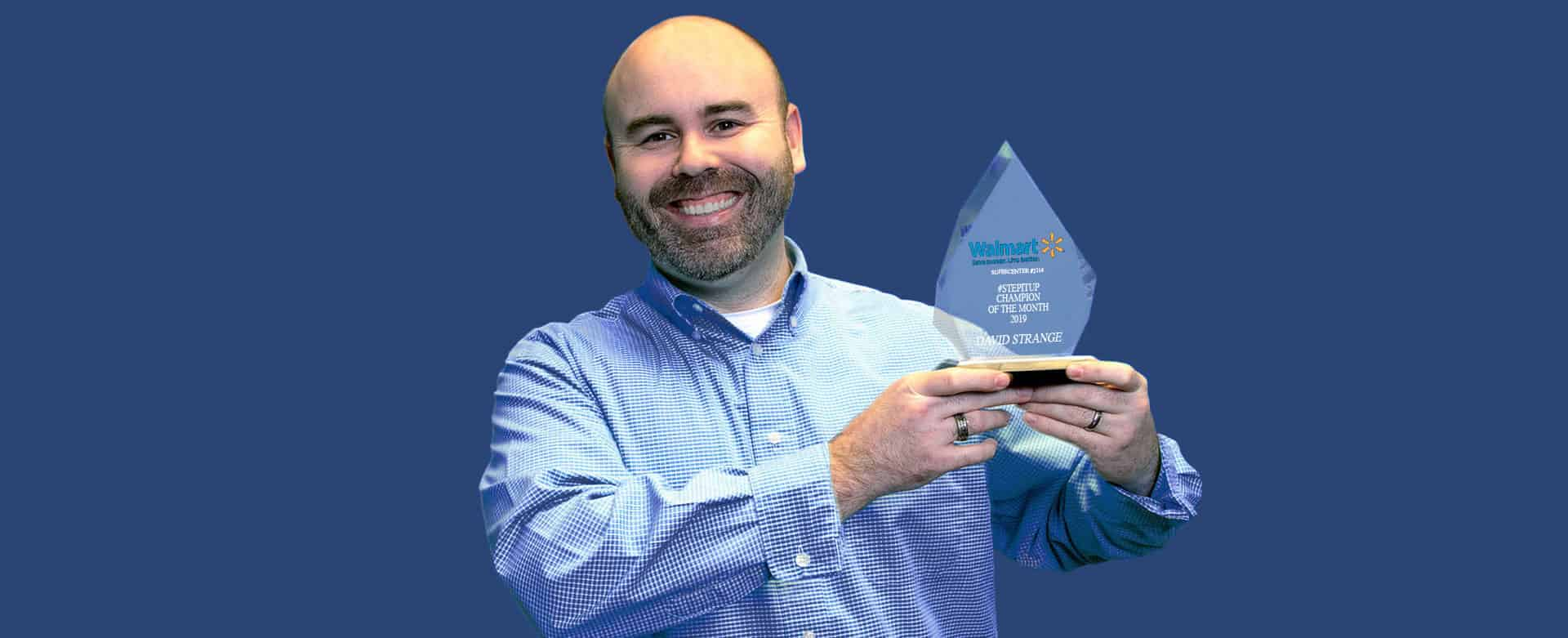 employee holding acrylic prism with Wal-mart logo on it